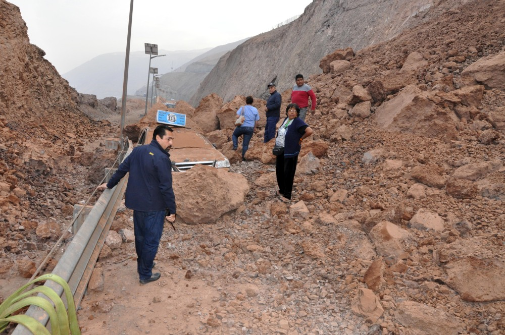 People walk across debris from a landslide which cut off the road access to the Chilean city of Iquique and town of Alto Hospicio Wednesday after the magnitude-8.2 earthquake.