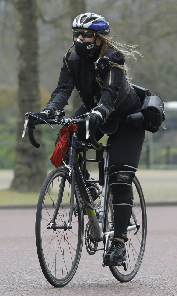 A cyclist wears a mask as she cycles along The Mall in London on Wednesday.