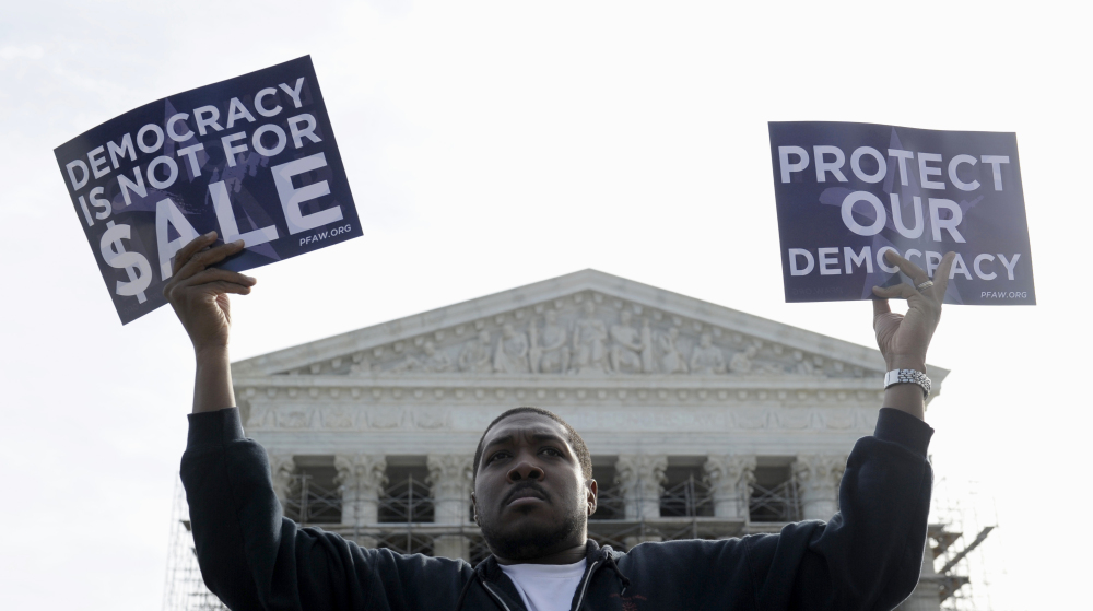Cornell Woolridge of Windsor Mill, Md., takes part in a demonstration outside the Supreme Court in Washington last fall when the court heard arguments on campaign finance. The Supreme Court struck down limits Wednesday in federal law on the overall campaign contributions the biggest individual donors may make to candidates, political parties and political action committees.