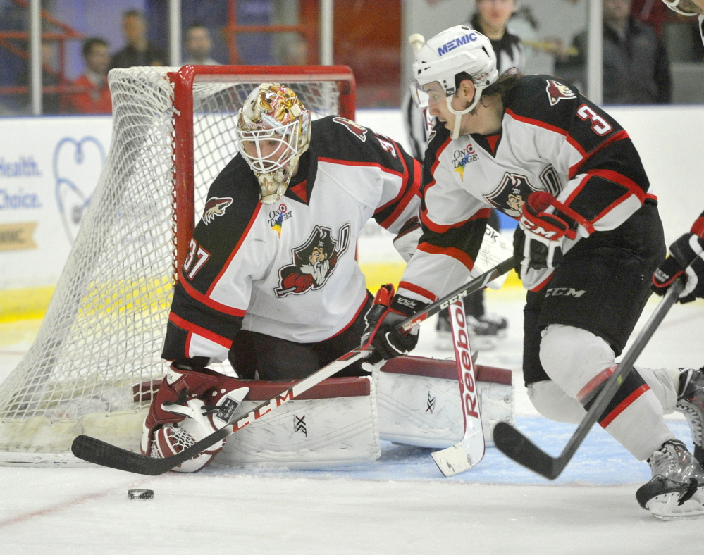 Pirate defenseman Daine Todd looks to clear a rebound after a save by goalie Louis Domingue.