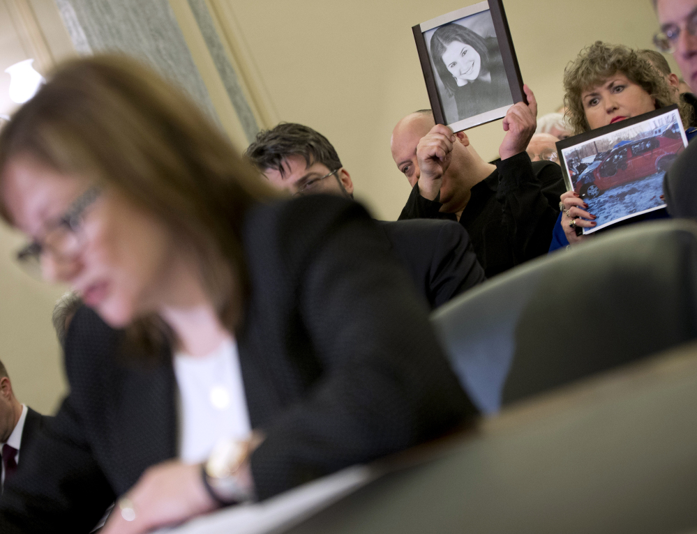 Leo Ruddy, center, and his wife Mary Theresa Ruddy, right, of Scranton, Pa., hold up photographs of their daughter Kelly Erin Ruddy and the 2005 Chevy Cobalt that she crashed and died in, as they sit in the audience to listen to testimony by General Motors CEO Mary Barra, left, on Capitol Hill in Washington on Wednesday before the Senate Commerce, Science and Transportation subcommittee.