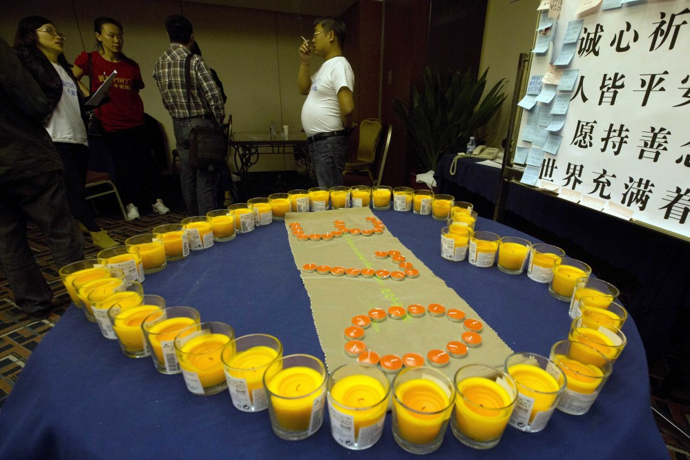 Relatives of Chinese passengers onboard the Malaysia Airlines MH370 stand near candles arranged as a memorial in a prayer room in Beijing, China, Thursday, April 3, 2014. No trace of the Boeing 777 has been found nearly a month after it vanished in the early hours of March 8 on a flight from Kuala Lumpur to Beijing with 239 people on board.