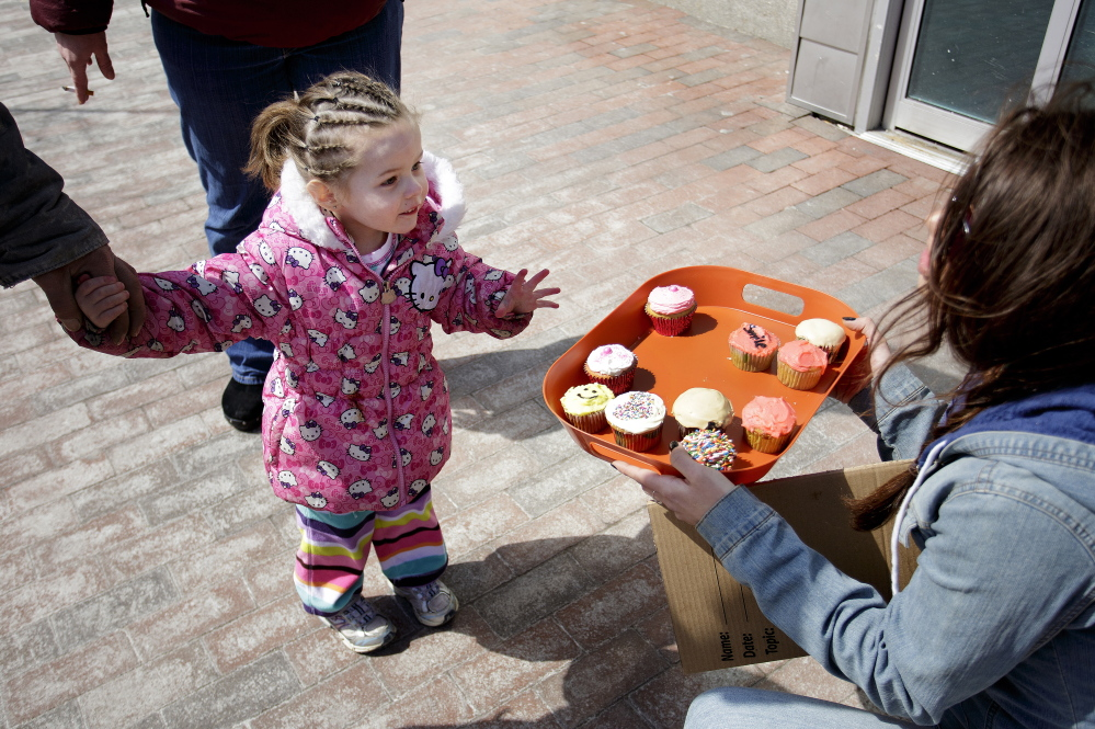 Shawna Torres, 3, of Portland ponders a difficult decision as she surveys the free cupcakes offered by Lindsy Bryce during an informal remembrance for Randee Bucknell on Congress Street Thursday.
