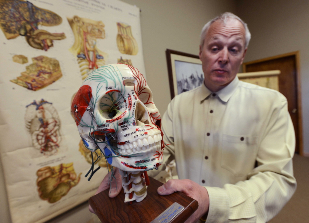 Dr. Tom Pliura holds an anatomical skull in his office in LeRoy, Ill. A cadaver lab sponsored by the McLean County Medical Society will be open to select students from advanced courses in subjects like anatomy and biology.