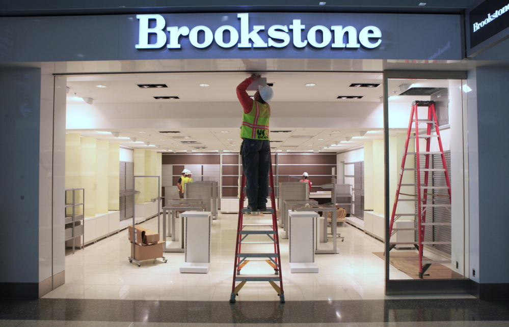 In this photo taken in September 2011, work is done on a light fixture at the Brookstone shop in a new terminal at the Sacramento International Airport in Sacramento, Calif. Brookstone, the retailer of gadgets such as virtual keyboards and personal drones, sought bankruptcy protection to pursue a sale to Spencer Spirit Holdings as consumers spend less on non-essentials.