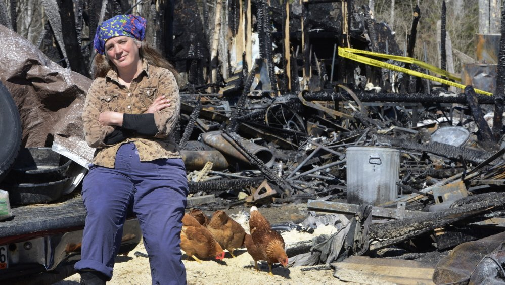 North Yarmouth farmer Jules Fecteau sits on the back of her truck against the backdrop of her barn that was destroyed by fire early Monday. The blaze was so destructive that the cause may never be determined for sure, a state fire investigator said Friday.