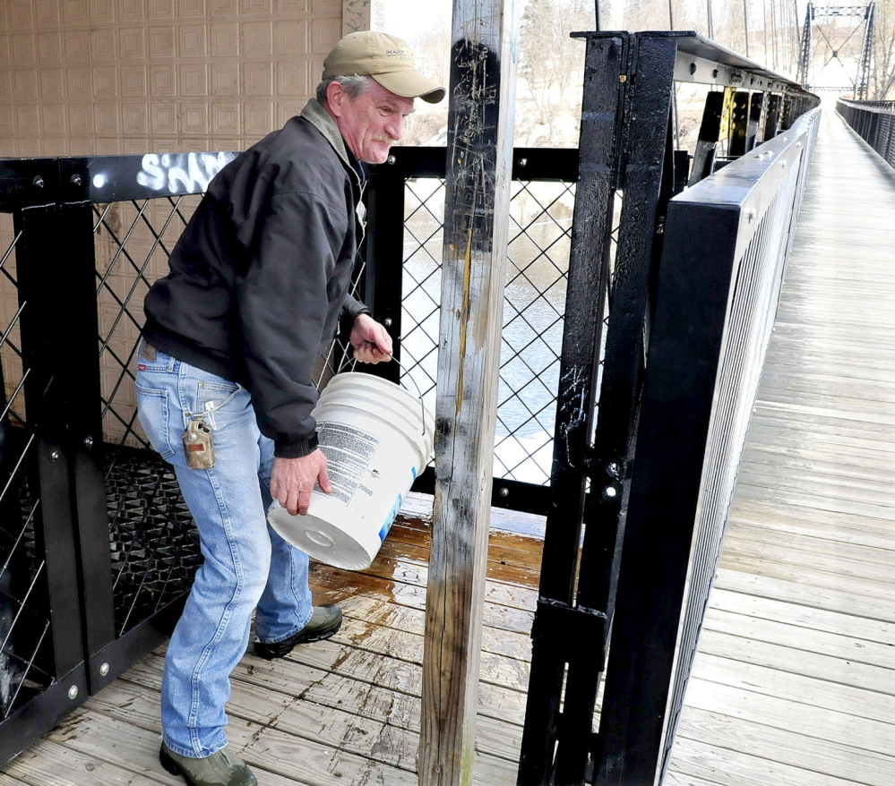 Staff photo by David Leaming CLEAN UP: David Nevedomsky of Winlsow uses a bucket of water to wash off human excrement that was left on the Waterville side of the Two-Cent bridge on Thursday. Nevedomsky said he is offended by the vandalism and expressed frustration that he did not get any assistance from officials on both sides of the river.