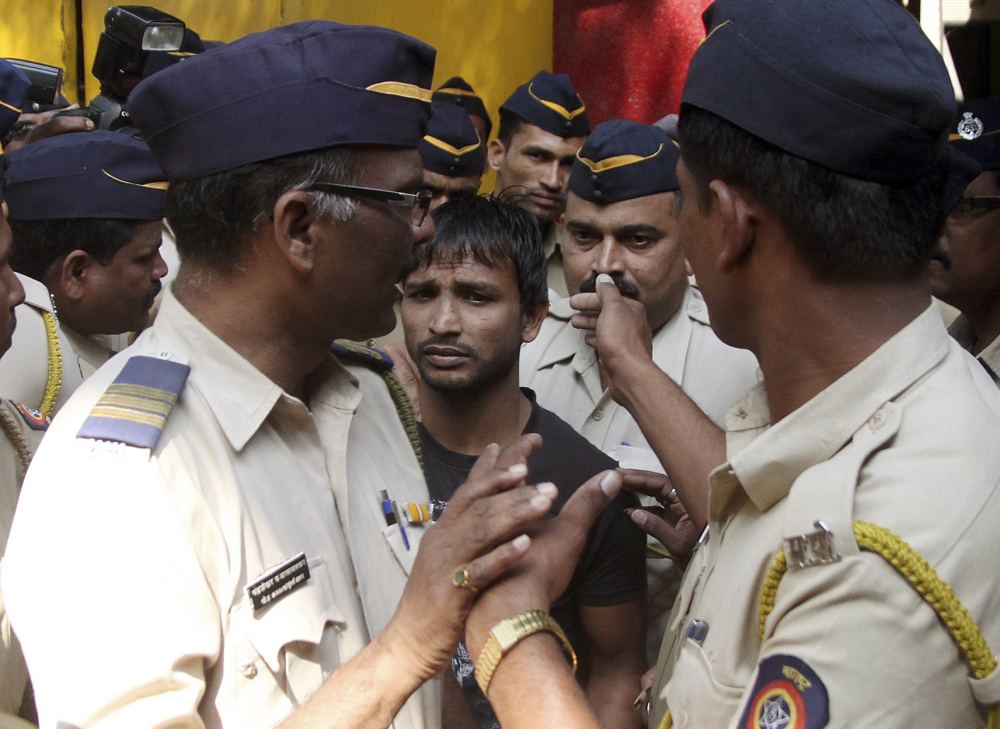 Police escort one of the four convicts in a gang rape to a court in Mumbai, India, on Friday. The court sentenced three of the men to death. A fourth got life in prison.