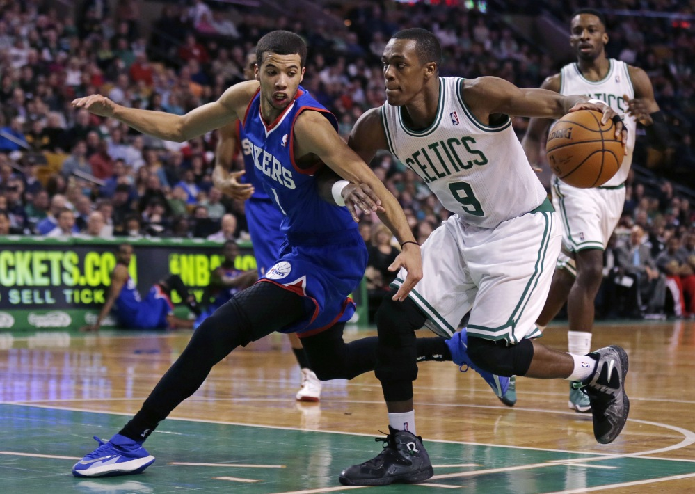 Philadelphia 76ers guard Michael Carter-Williams, left, tries to stop Boston Celtics guard Rajon Rondo on a drive to the basket during the second quarter of Friday's NBA game in Boston.