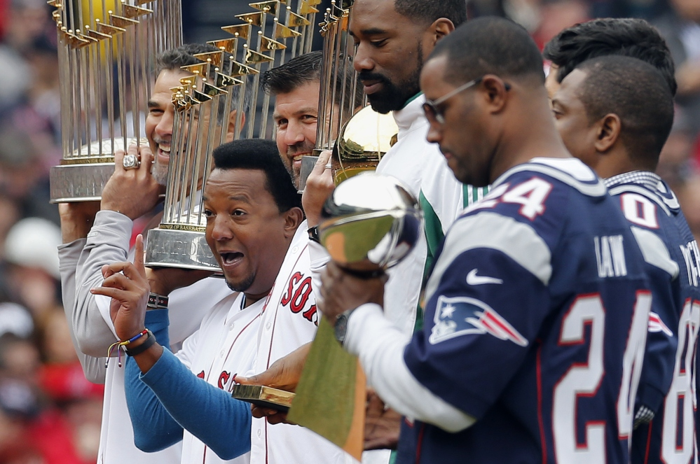 Former Boston Red Sox player Pedro Martinez, second from left, stands with Mike Lowell, left, Jason Varitek, former Boston Celtics' Leon Powe, fourth from left, and former players from the New England Patriots during pre-game ceremonies before a baseball game against the Milwaukee Brewers on bpening day at Fenway Park in Boston on Friday.