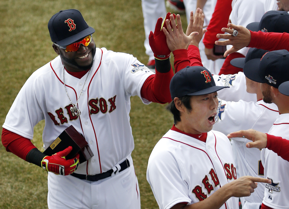 Boston Red Sox designated hitter David Ortiz, left, and relief pitcher Koji Uehara, lower right, celebrate with teammates after receiving their 2013 World Series rings at Fenway Park in Boston on Friday during home opening day ceremonies prior to a baseball game between the Boston Red Sox and the Milwaukee Brewers.