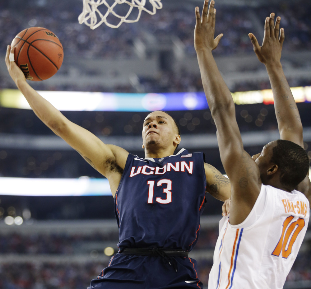 Connecticut guard Shabazz Napier (13) shoots as Florida forward Dorian Finney-Smith (10) defends during the first half of the NCAA Final Four tournament college basketball semifinal game Saturday.