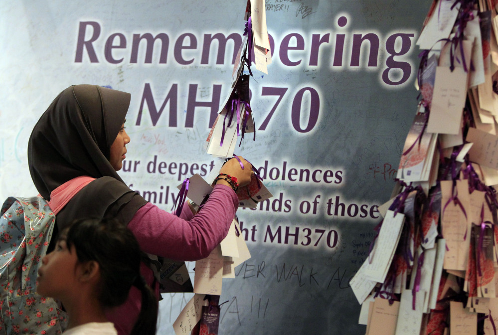 A woman ties a message for passengers aboard the missing Malaysia Airlines flight MH370, at a shopping mall in Kuala Lumpur, Malaysia, on Saturday. Search teams racing against time to find the flight recorders from the missing Malaysia Airlines jet crisscrossed another patch of the Indian Ocean on Saturday, four weeks to the day after the airliner vanished.