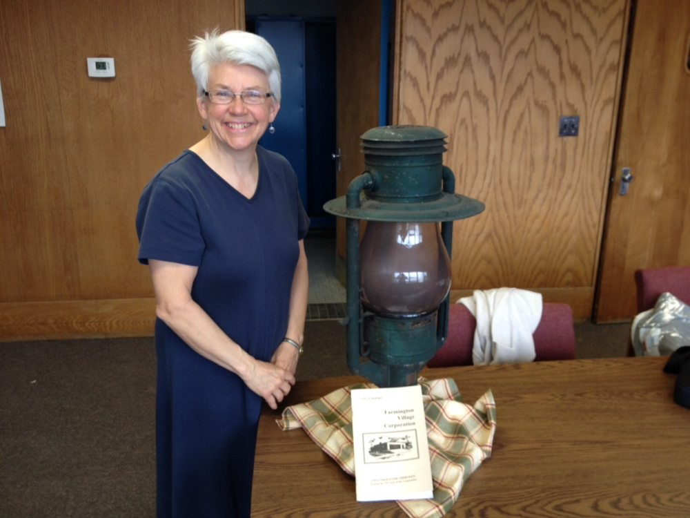 Jane Woodman, business manager for the Farmington Village Corporation, stands next to a 130-year-old lamp that came from an era when the corporation, not the town, ran the municipal streetlights.