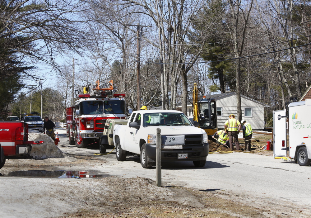 Workers replace a valve on a gas line after a gas leak on Abby Road in North Windham on Sunday. Four homes were evacuated Sunday morning.