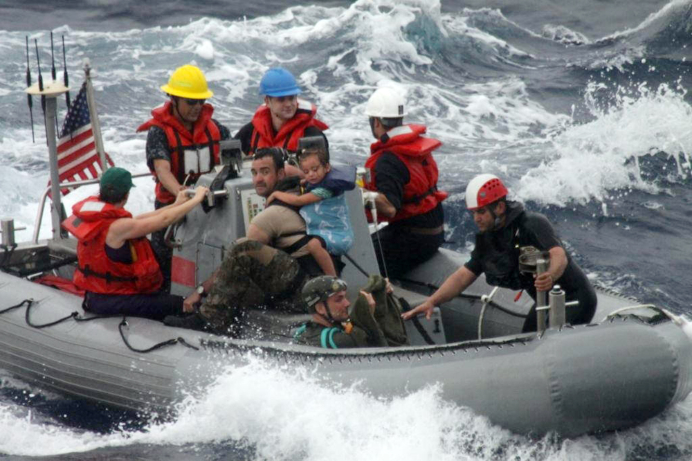In this photo provided by the U.S. Coast Guard, sailors from Oliver Hazard Perry-class frigate USS Vandegrift assist in the rescue Sunday of a family with a sick infant as part of a joint U.S. Navy, Coast Guard and California Air National Guard rescue effort.