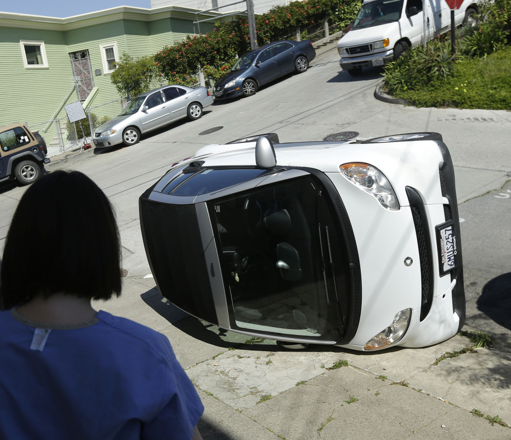 Shelley Gallivan looks toward a tipped-over Smart car in San Francisco. Police are investigating why four Smart cars were flipped over Monday during an apparent vandalism spree.