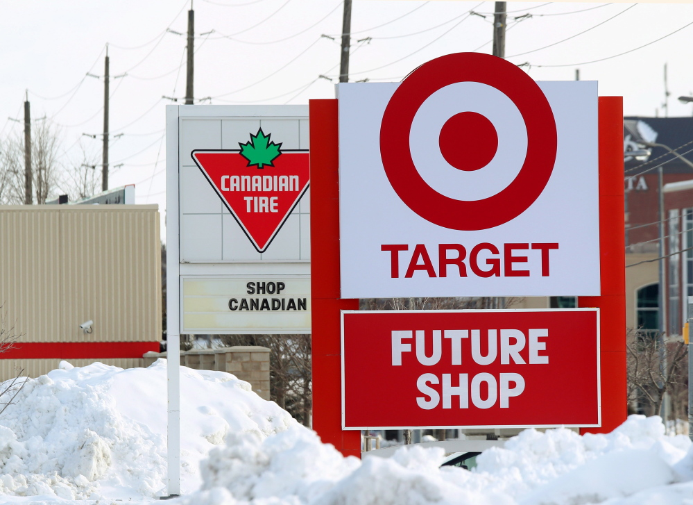 Snow is piled in the parking lot of the new Target store in Guelph, Ontario, as Canadian Tire posts a Canadian message on their sign. Canadian Tire, which operates nearly 500 stores in the country and stocks housewares, barbecue grills and other items besides tires, has increased its marketing and deepened its inventory of home decor to compete with Target.