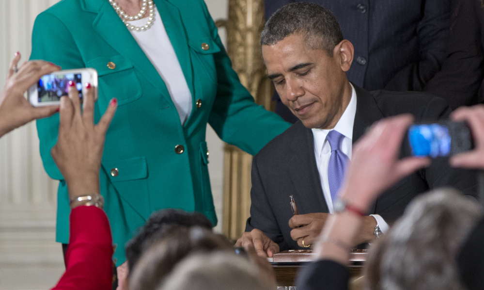 As members of the audience take photos, President Barack Obama signs new executive actions to strengthen enforcement of equal pay laws for women on Tuesday in the East Room of the White House during an event marking Equal Pay Day.