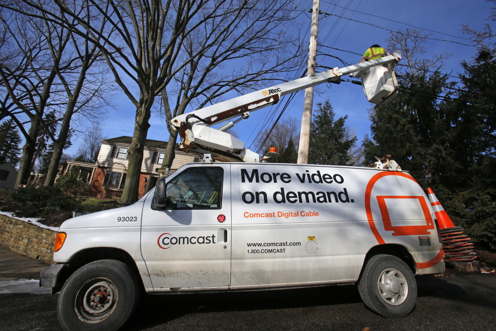 A Comcast cable truck works in front of a home in Mount Lebanon, Pa., recently. Comcast says it will provide its Internet Essentials program, offering Web access for $9.95 monthly to low-income families, in former Time Warner markets.