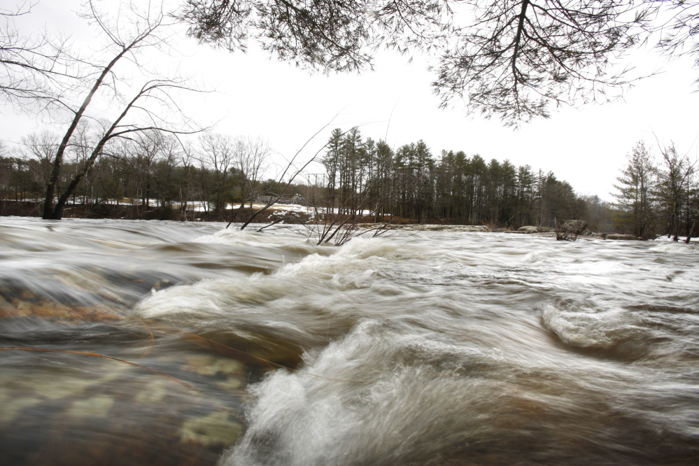 On the Saco River in Standish on Tuesday, water flows over rocks that are normally above water. Flooding from heavy rains on Monday was minimal.