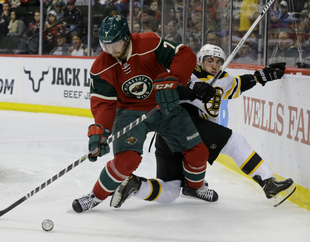 Wild defenseman Jonathon Blum fights off Boston's Brad Marchand for the puck in the second period Tuesday night in St. Paul, Minn. The Wild rallied to win 4-3 in a shootout to clinch a playoff berth.