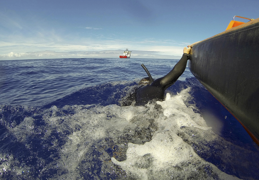 Able Seaman Clearance Diver Michael Arnold is towed by a fast-response craft from the Australian Defense's ship Ocean Shield as he scans the water for debris of the missing Malaysia Airlines Flight 370 in the southern Indian Ocean on Monday.