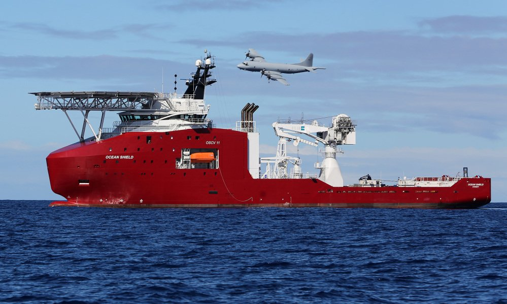 In this photo provided by the Australian Defense Force, a Royal Australian Air Force AP-3C Orion flies past Australian Defense vessel Ocean Shield Wednesday on a mission to drop sonar buoys to assist in the acoustic search of the missing Malaysia Airlines Flight 370 in the southern Indian Ocean.