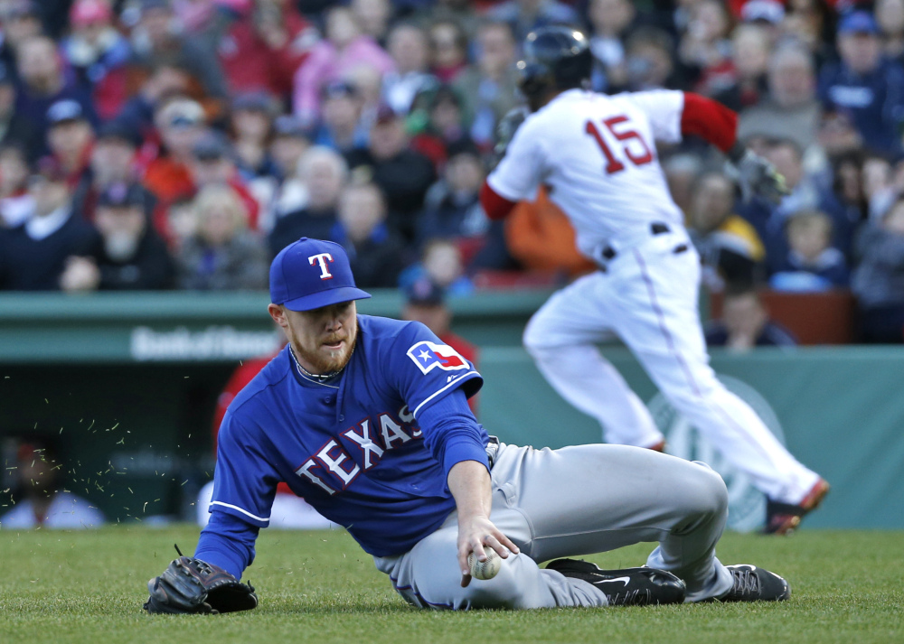 Texas Rangers starting pitcher Robbie Ross slides to field a ground ball single by Boston Red Sox's Dustin Pedroia (15) in the third inning of a baseball game at Fenway Park in Boston, Wednesday, April 9, 2014.
