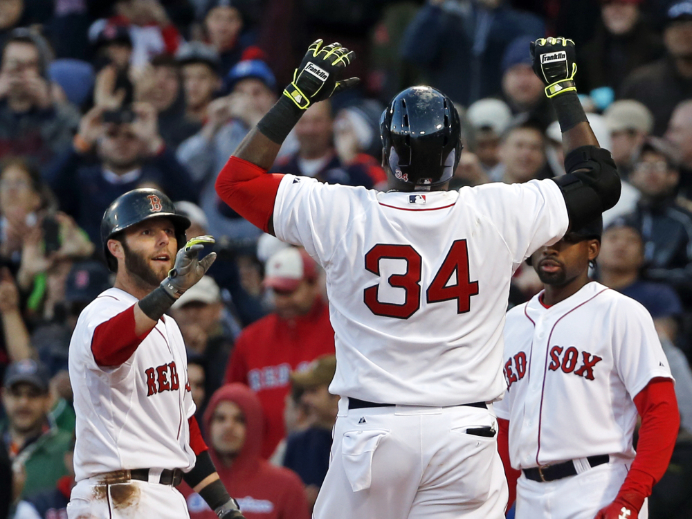 Boston Red Sox's David Ortiz (34) celebrates at the plate after hitting a three-run homer, scoring Dustin Pedroia, left, and Jackie Bradley Jr., right, in the eighth inning of a baseball game against the Texas Rangers at Fenway Park in Boston, Wednesday, April 9, 2014. The Red Sox won 4-2.