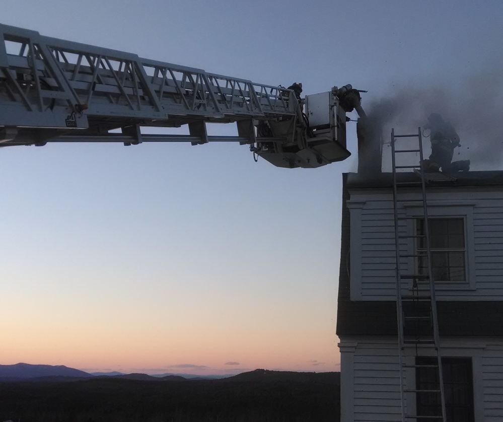 Firefighters work to douse a chimney fire that spread, causing extensive damage to this century-old farmhouse at 42 Orchard Road in Sebago on Wednesday night.