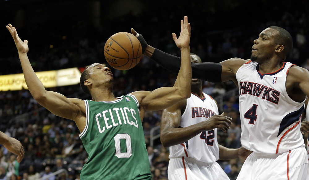 Paul Millsap of the Atlanta Hawks, right, reaches for a loose ball against Avery Bradley of the Boston Celtics in the fourth quarter of Atlanta's 105-97 victory Wednesday night.