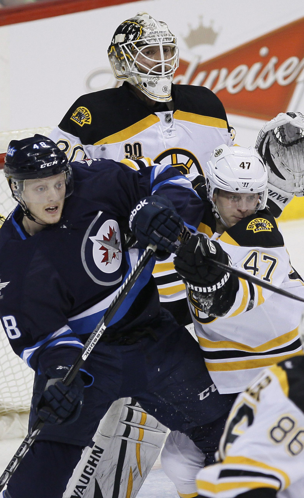 Boston's Torey Krug tries to clear Winnipeg's Carl Klingberg from in front of goaltender Chad Johnson during Thursday's game in Winnipeg, won by the Jets.