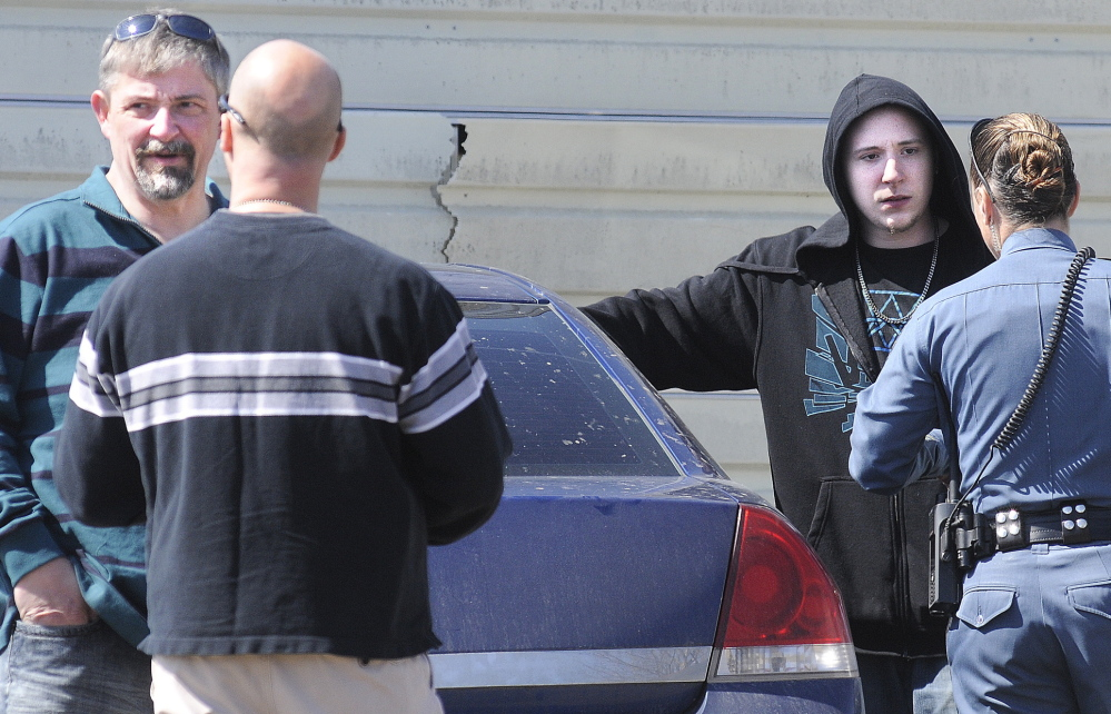 Frederick Horne Sr., left, and Frederick Horne Jr. speak with Maine State Police officers Thursday after being cited on charges of sex trafficking at their Sidney residence.