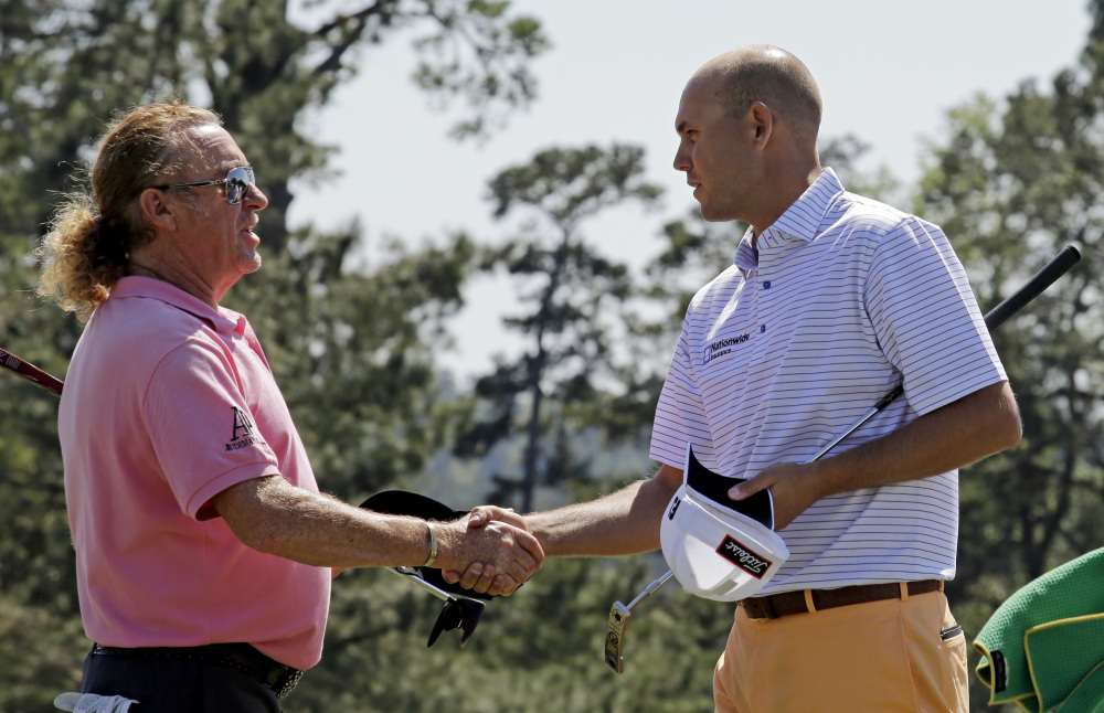 Miguel Angel Jimenez, of Spain, shakes hands with Bill Haas, right, on the 18th green following their first round of the Masters golf tournament Thursday in Augusta, Ga.