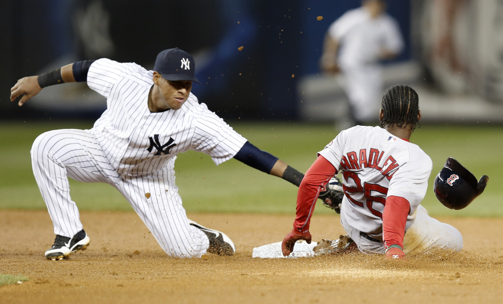 Boston Red Sox's Jackie Bradley Jr. is safe sliding into second base on a third-inning stolen base as Yankees third baseman Yangervis Solarte applies the tag but loses the ball.