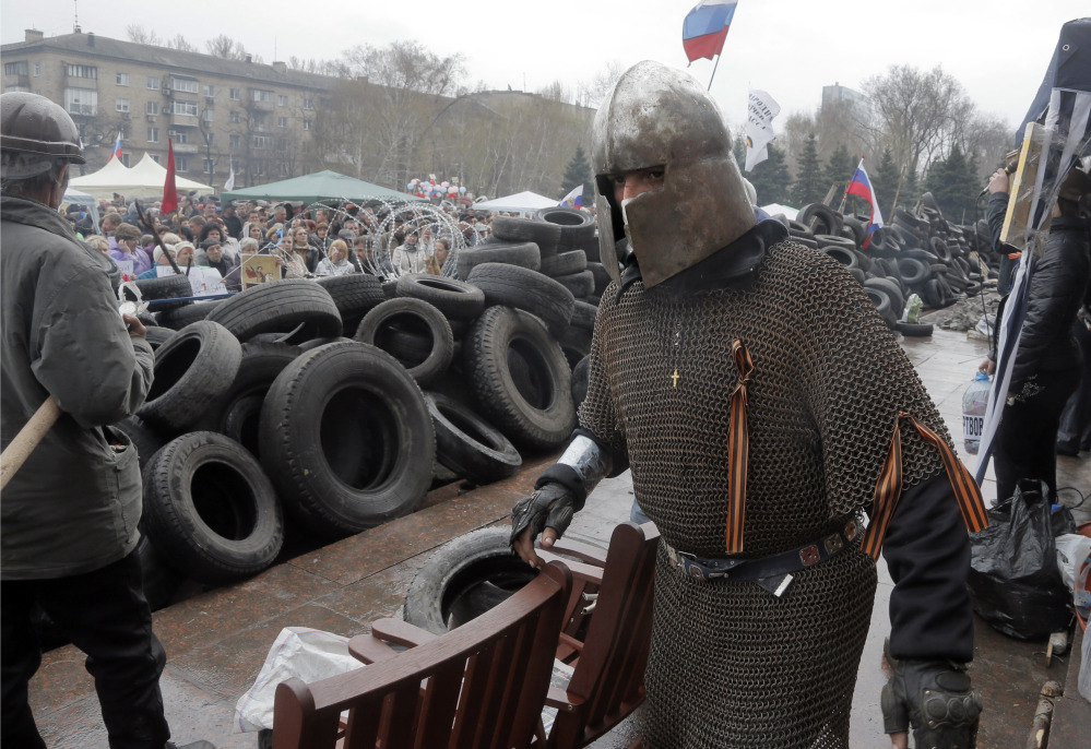 A pro-Russian activist dressed as a knight guards the barricade at the regional administration building that was seized earlier in Donetsk, Ukraine, on Thursday, as protests continued to flare up across Ukraine's industrial heartland.