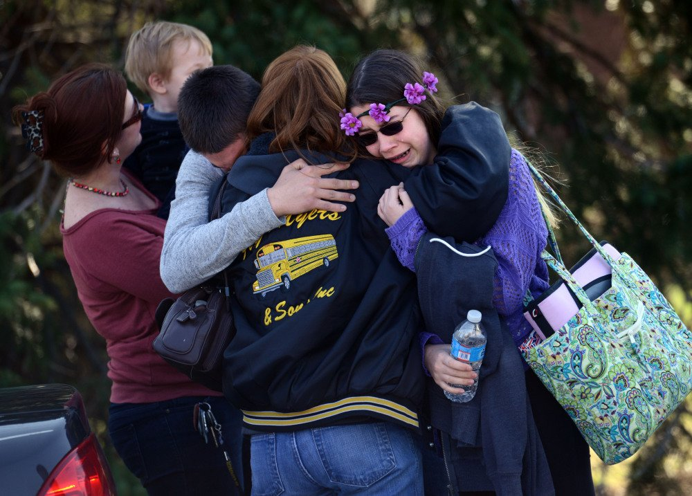 Parents and students embrace near Franklin Regional High School after 21 students and a security guard were injured in an attack by a knife wielding suspect Wednesday in Murrysville, Pa., near Pittsburgh.