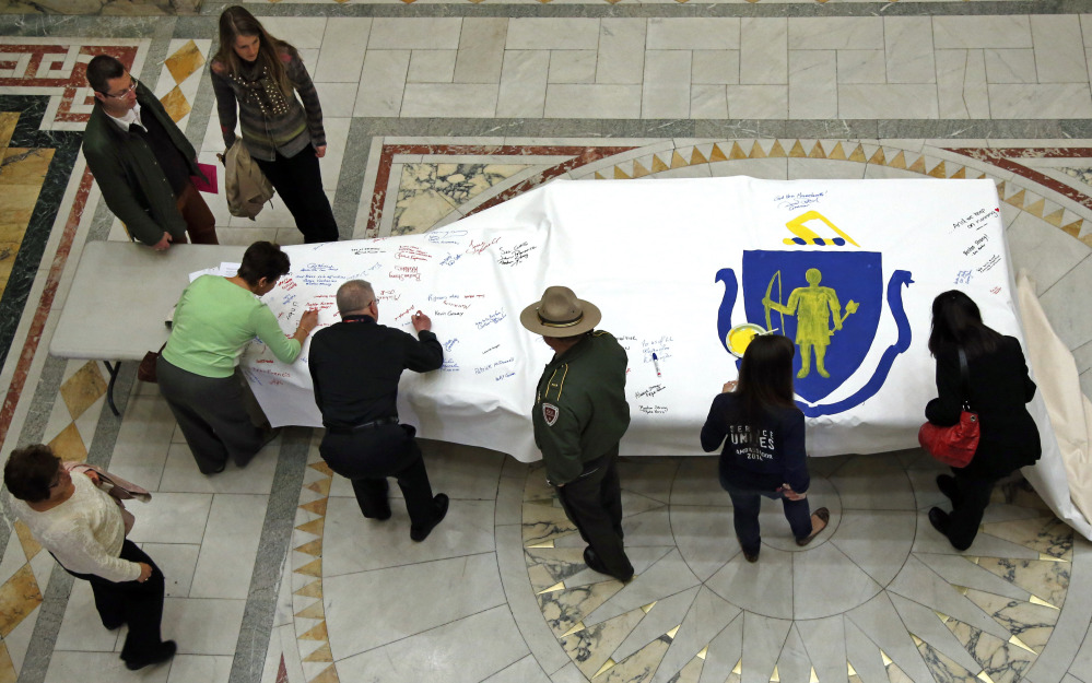 People sign the America 4 Boston Prayer Canvas at the Statehouse in Boston in memory of marathon bombing victims.