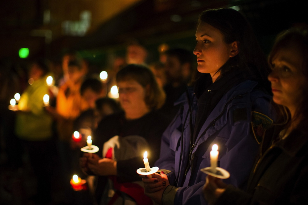 """People hold a candlelight vigil April 5 at the Darrington Community Center. """"Even someone who does not believe in God lifts up their eyes and asks """"Why?' a chaplain says"""