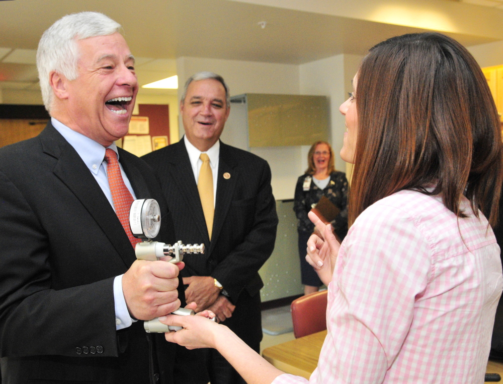 Rep. Mike Michaud, D-2nd District, left, laughs with occupational therapist Heidi Kelly, as she shows him a grip strength tester during a tour of the VA Maine Healthcare Systems-Togus on Friday. Michaud was joined on the tour by the chairman of the House Veterans' Affairs Committee Rep. Jeff Miller, R-Fla., center.