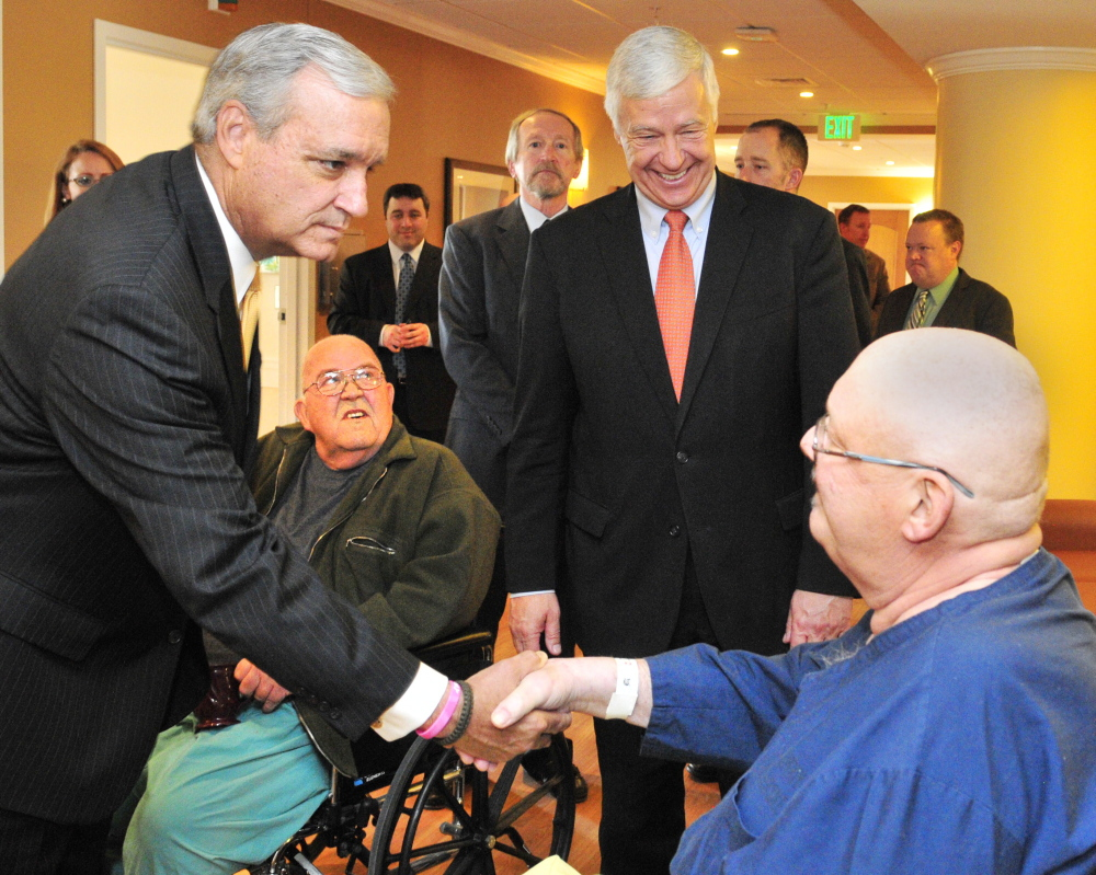 U.S. Rep. Jeff Miller, R-Fla., left, shakes hands with Bruce Pray of Winthrop during a tour Friday of the VA hospital at Togus, as U.S. Rep. Mike Michaud, D-Maine, looks on.