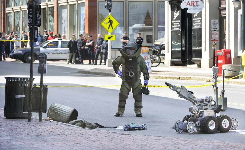 A Portland police bomb squad member and robot remove a device from a trash can Friday morning at the CVS drugstore at 510 Congress St. The device, used during a robbery, resembled a bomb but was found not to be explosive.