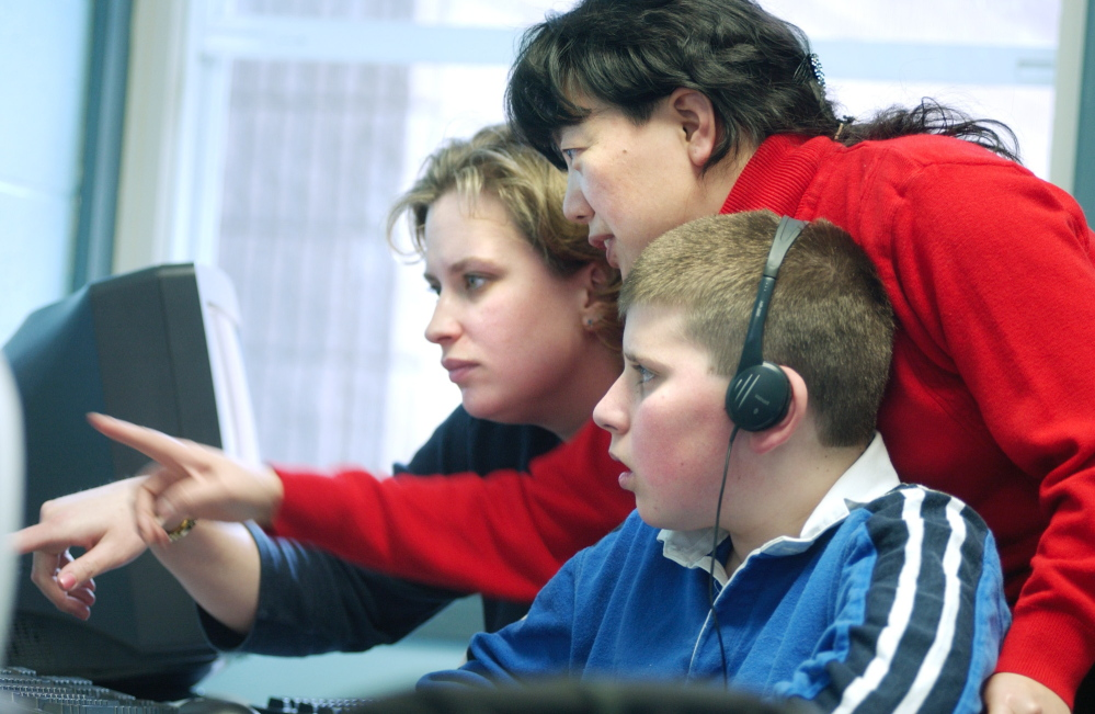 Yuhong Sun, center, the computer teacher at Pownal Elementary School, helps sixth-grader Mac Jordan and educational technician Nikki Blackstone work through a problem during a recent computer class.