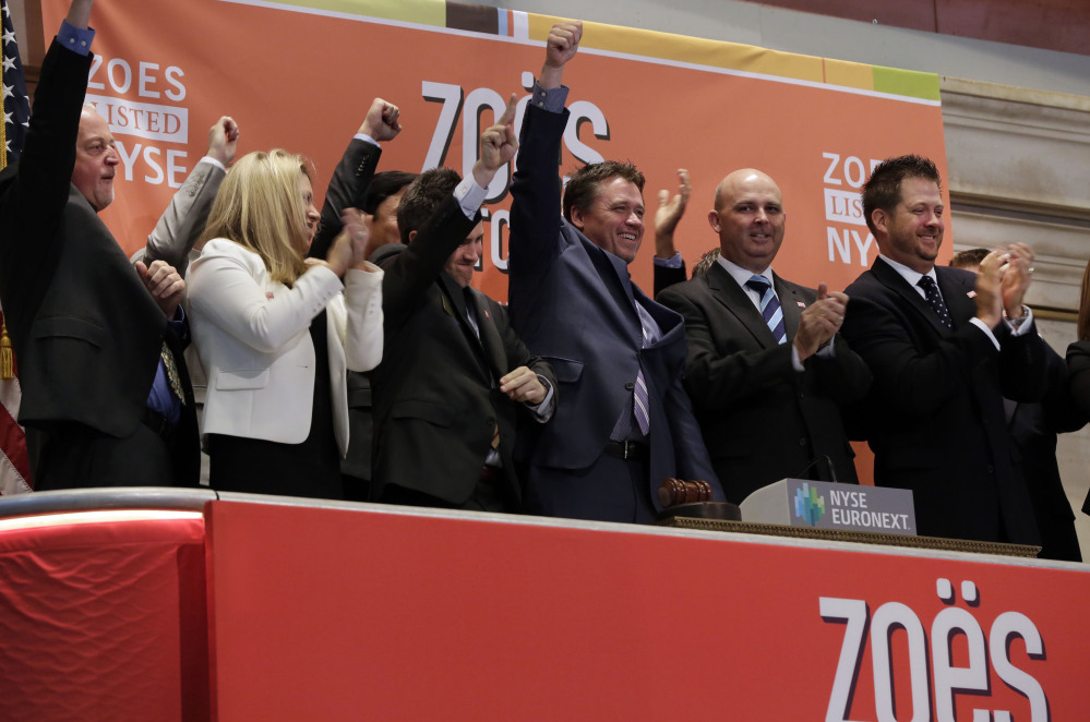 Zoe's Kitchen President and CEO Kevin Miles, center, celebrates as he rings the New York Stock Exchange opening bell, marking his company's IPO on Friday.