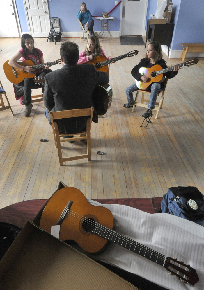 Guitar teacher Don Pride works with students at Mayo Street Arts, which is teaming with the Portland Conservatory of Music to bring music education to students in the Bayside area of Portland.