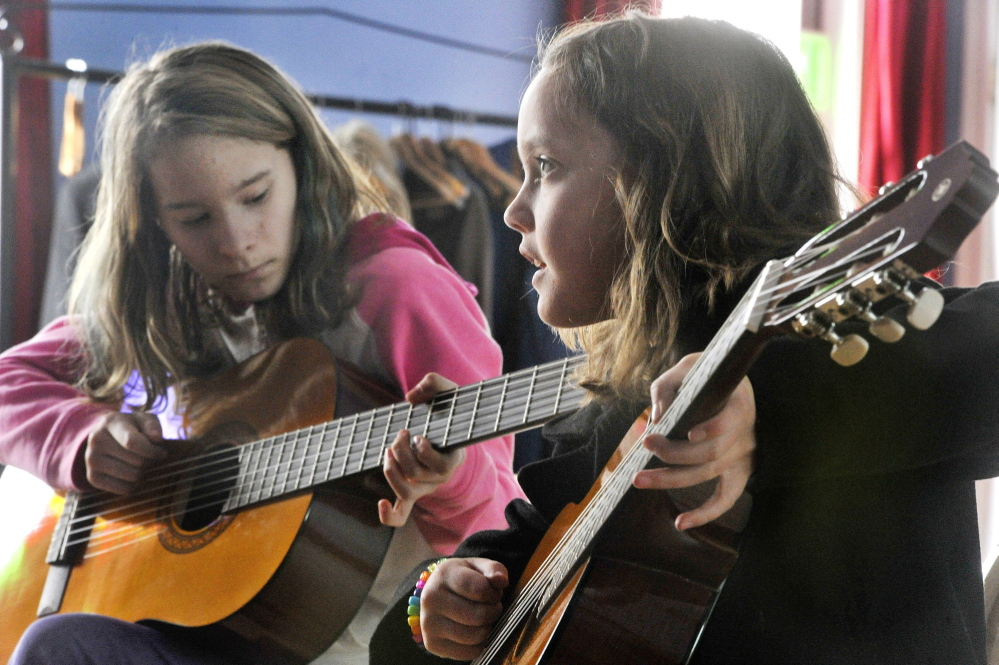 Guitar students Maya DeSouza, left, and Aoife Mahoney practice during a recent lesson at Mayo Street Arts.