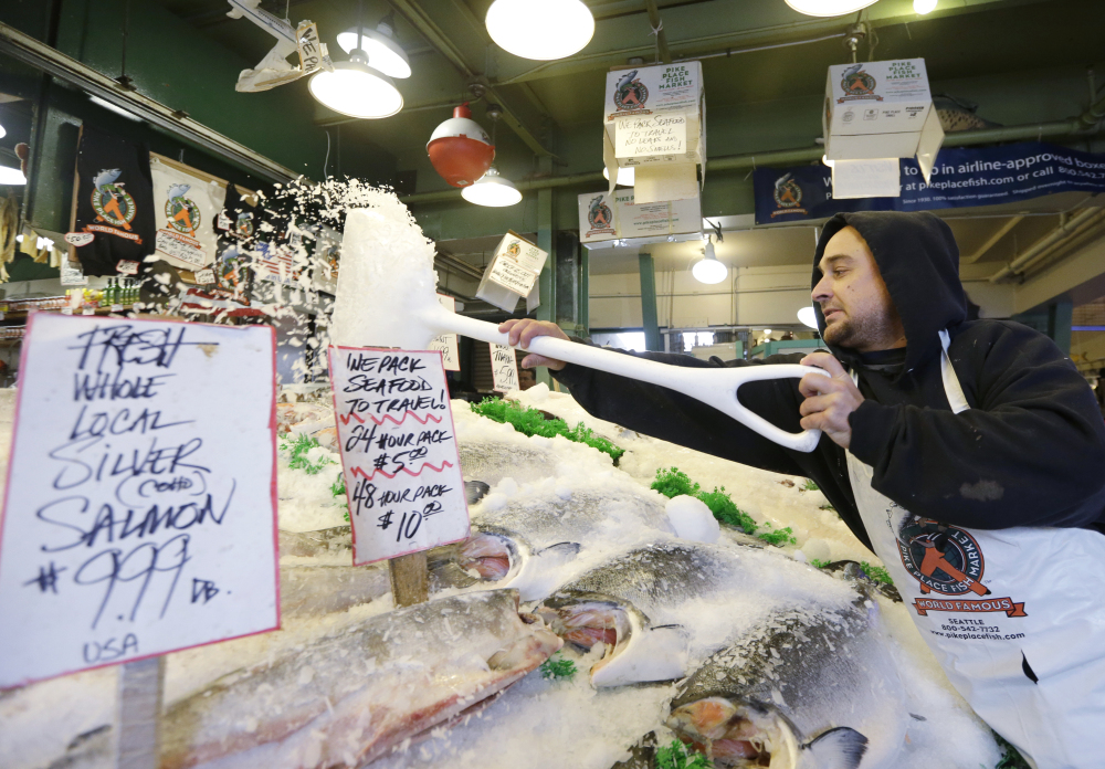 Fishmonger Erik Espinoza shovels ice onto fresh fish at the Pike Place Market in Seattle. Lawmakers in both state legislatures and in Washington, D.C., have been considering bills to help to ensure more accurate labeling of seafood.