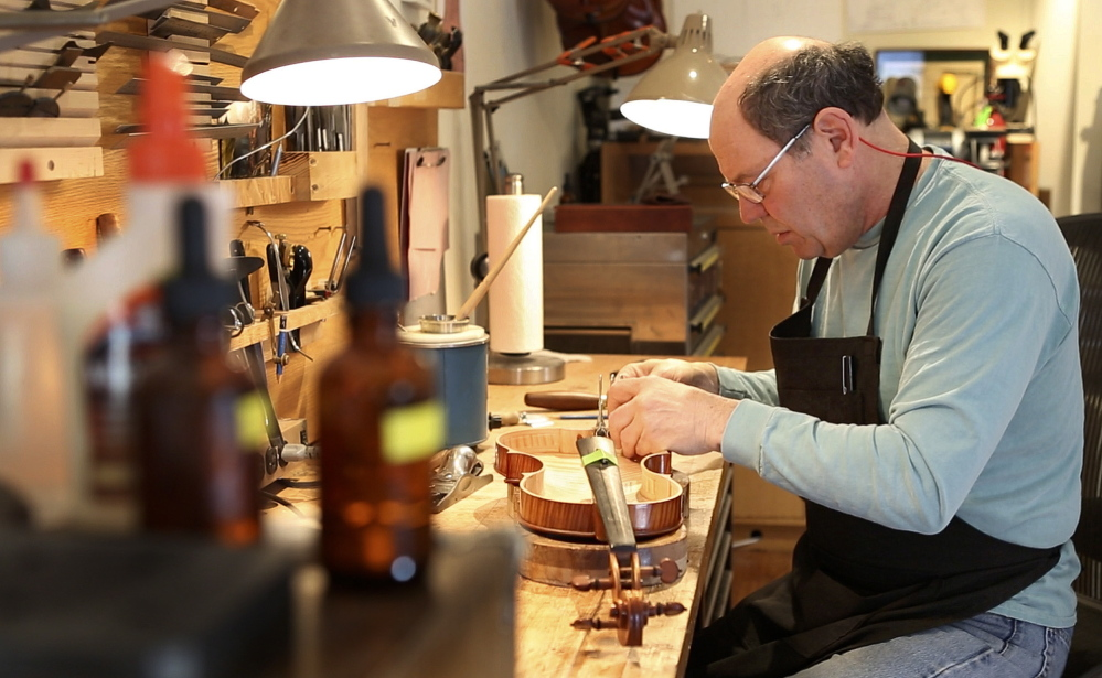 Jonathan Cooper repairs a violin owned by Mark O'Connor, one of the world's pre-eminent violinists.