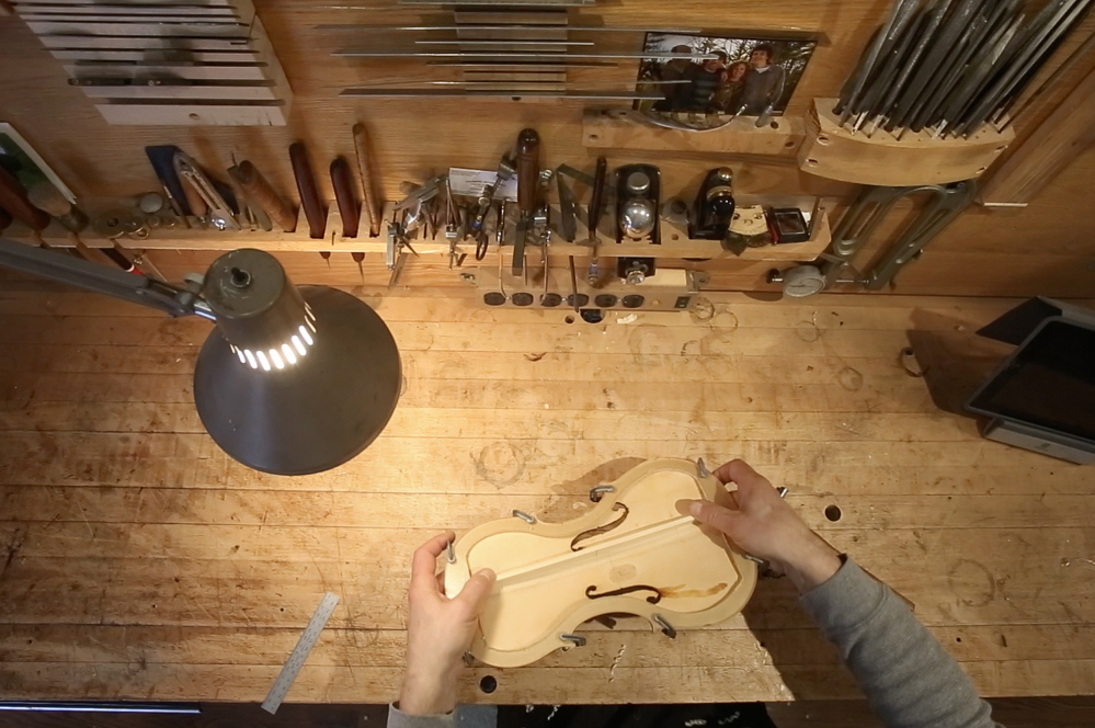 Jonathan Cooper tests the seating of the new bass bar on the inside top of Mark O'Connor's violin Thursday. The bass bar's placement and design influence the timbre of the instrument and give character to the violin's sound.